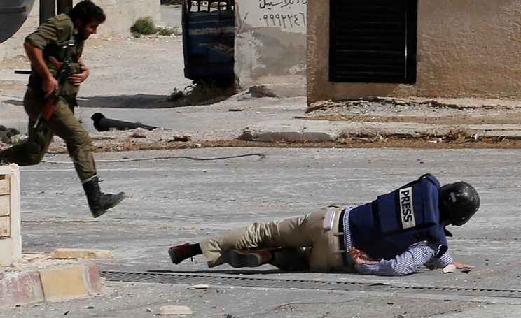 TO GO WITH AFP STORY SYRIA-CONFLICT-MEDIA (FILES) AFP reporter Sammy Ketz, hits the ground as a Syrian soldier runs past during snipper fire in the ancient Christian Syrian town of Maalula, on September 18, 2013. Journalists in Syria have been killed by snipers, accused of spying, and kidnapped by gunmen, and with the threats growing, many say the conflict is now too dangerous to cover. Media watchdog Reporters Without Borders (RSF) says at least 25 professional journalists and 70 citizen journalists have been killed in the conflict.  AFP PHOTO/ANWAR AMRO          (Photo credit should read ANWAR AMRO/AFP/Getty Images)