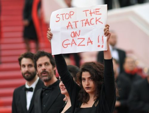 "TOPSHOT - French-Lebanese actress Manal Issa (R) holds a sign reading ""Stop the Attack on Gaza"" as she arrives on May 15, 2018 with Syrian director Gaya Jiji (2ndR) and Greek-South African film director Etienne Kallos (2ndL) for the screening of the film ""Solo : A Star Wars Story"" at the 71st edition of the Cannes Film Festival in Cannes, southern France. (Photo by LOIC VENANCE / AFP)        (Photo credit should read LOIC VENANCE/AFP/Getty Images)"